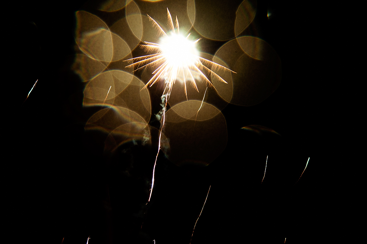 Firework with rain droplets on the lens